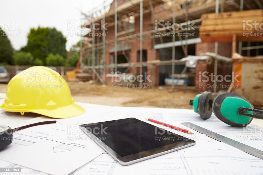 Close Up Of Plans And Digital Tablet On Building Site stock photo