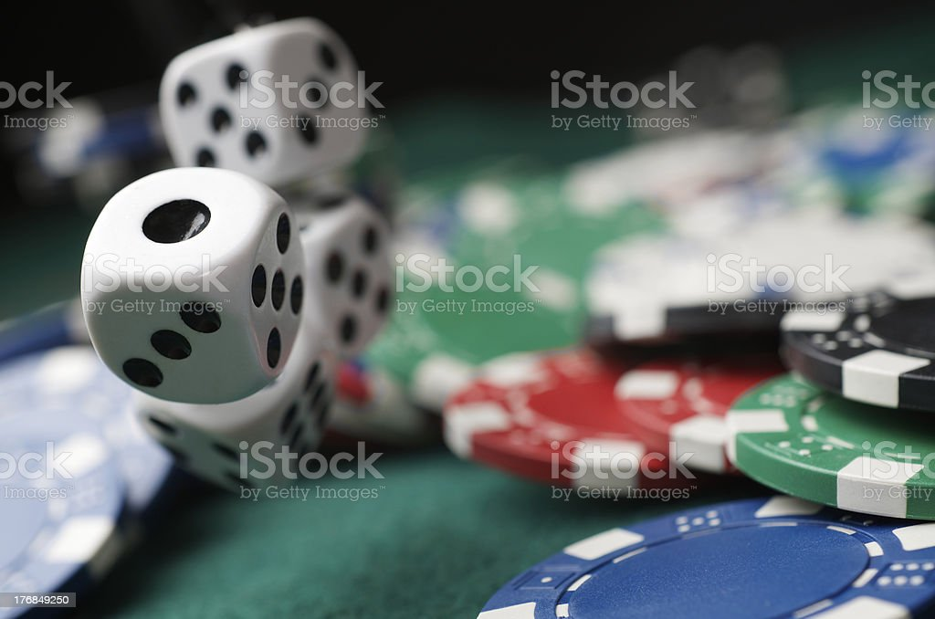 Close up of poker chips & dice being thrown at poker table stock photo