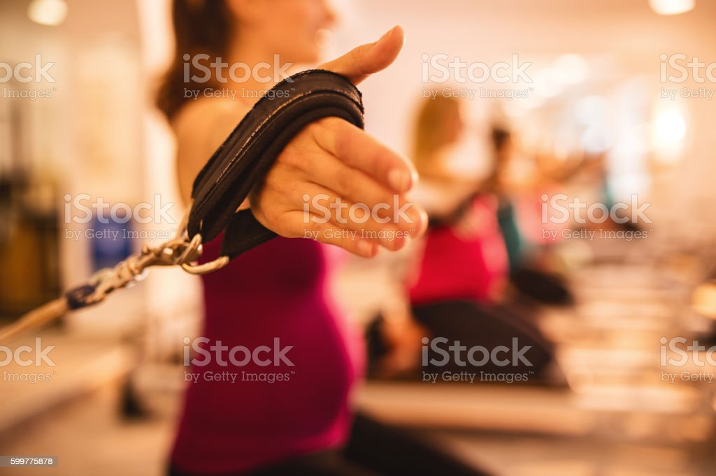 Close up of pregnant woman exercising on Pilates machine. stock photo