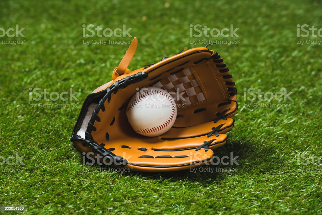 close up of professional baseball glove with ball on green grass stock photo