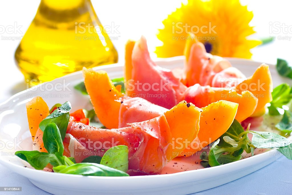 Close up of prosciutto con melons on white dish royalty-free stock photo