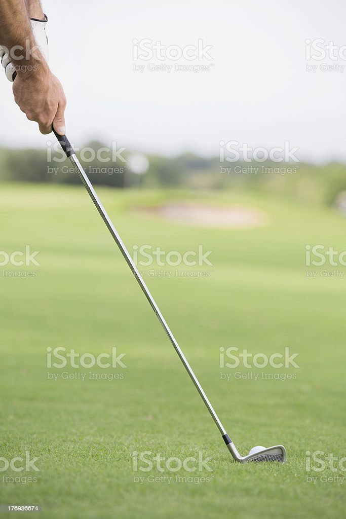 Close up of putter hitting golf ball on green course stock photo