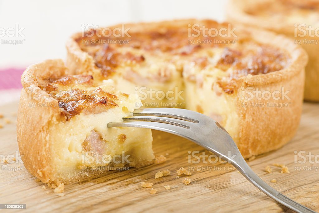 Close up of quiche with fork on wooden board stock photo