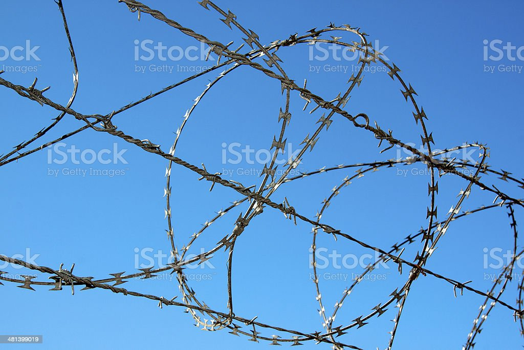 Close up of Razor Security Fence Against Blue Sky stock photo