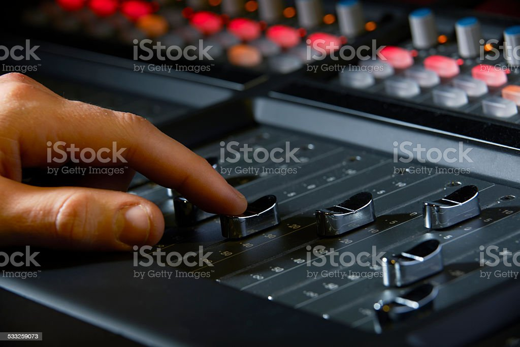 Close Up Of Recording Engineer Pushing Fader In Studio stock photo