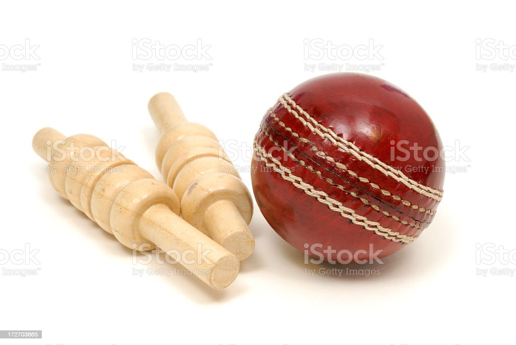 Close up of red leather cricket ball and two wooden bails  stock photo