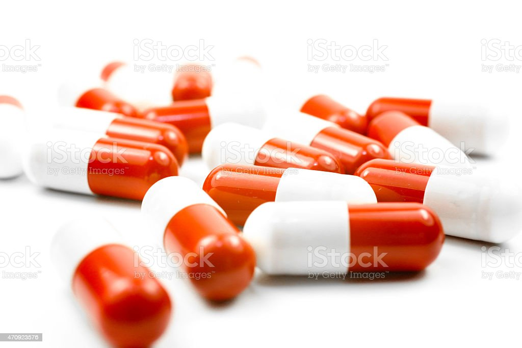 Close up of red medical capsules isolated on white background stock photo
