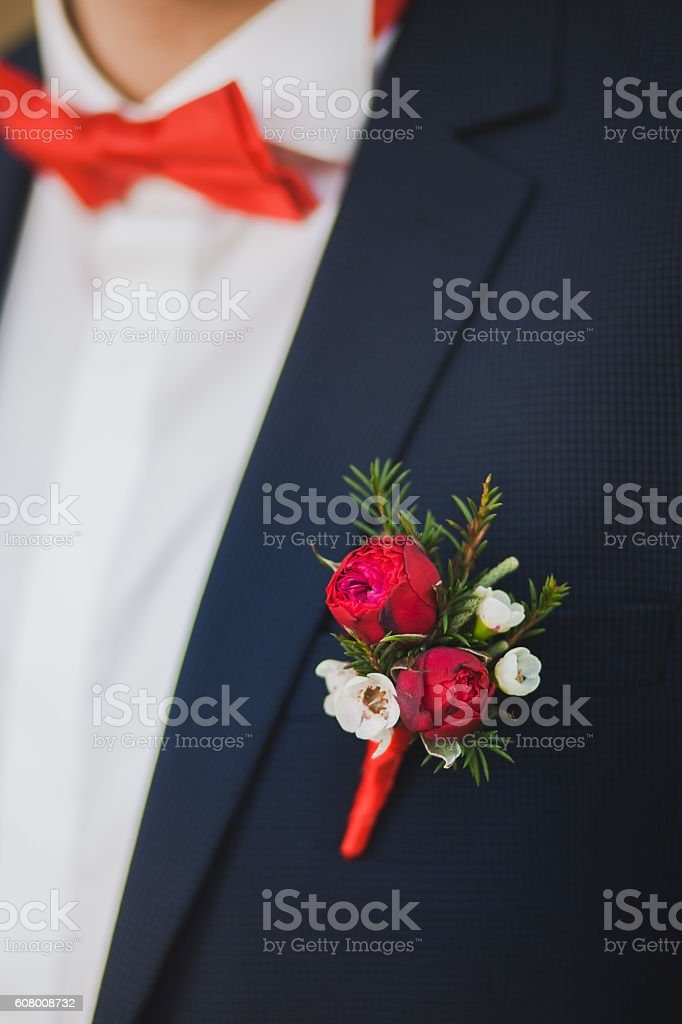 Close up of red rose corsage on man suit stock photo