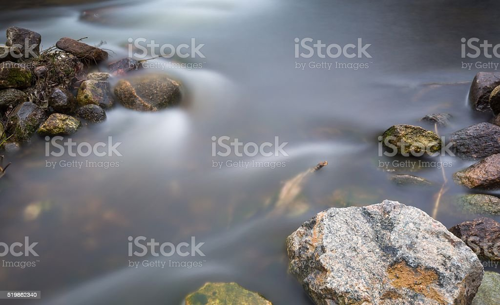 Close up of river with stones and plants stock photo