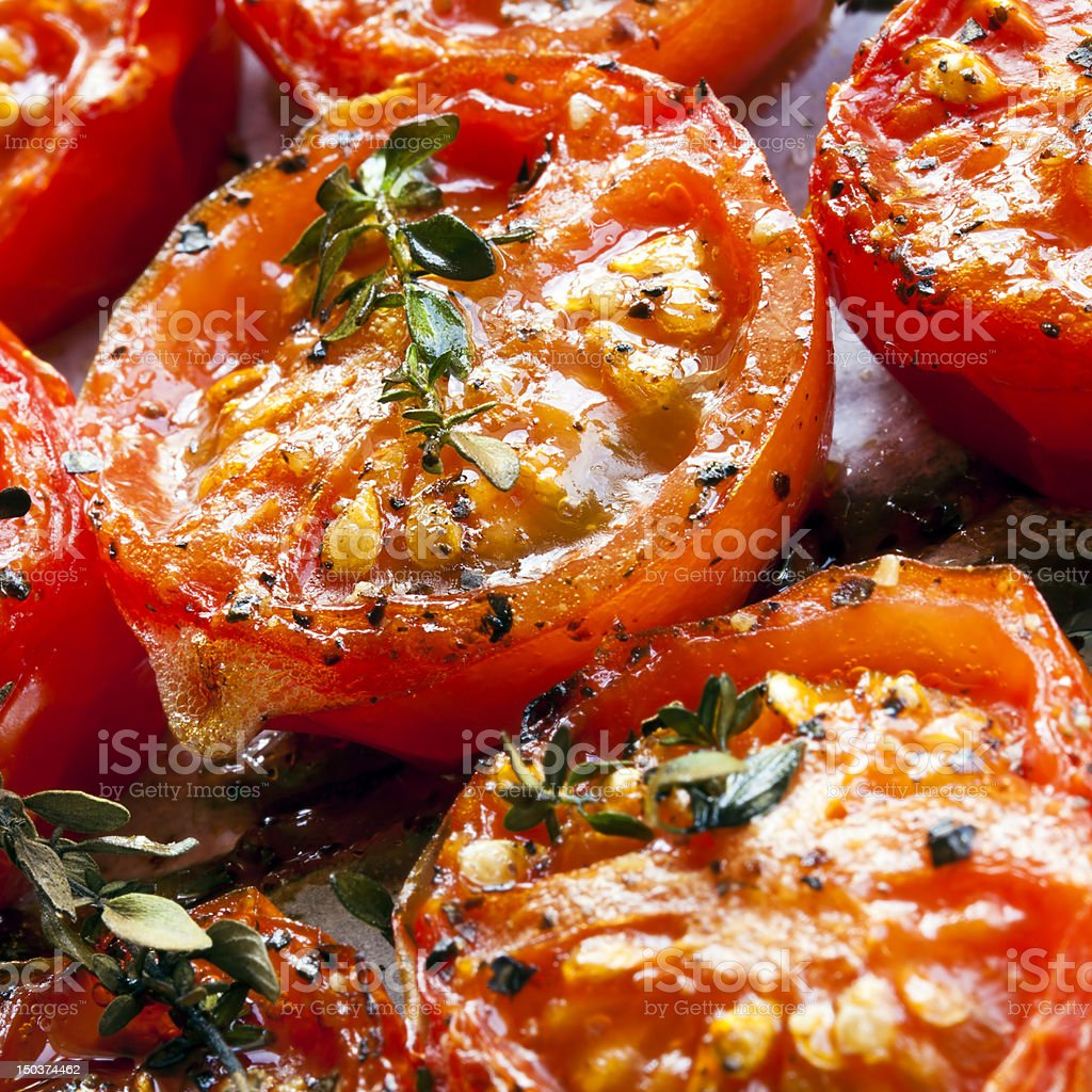 Close up of roasted red cherry tomatoes seasoned stock photo