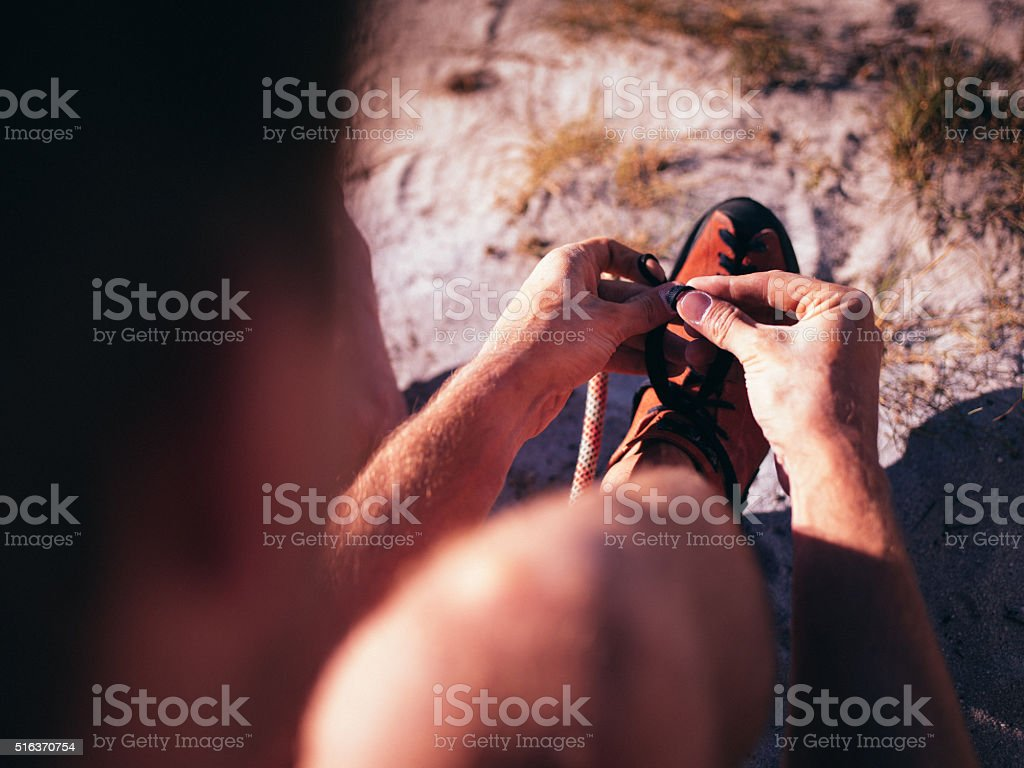 Close up of rock climber tying laces on climbing shoes stock photo