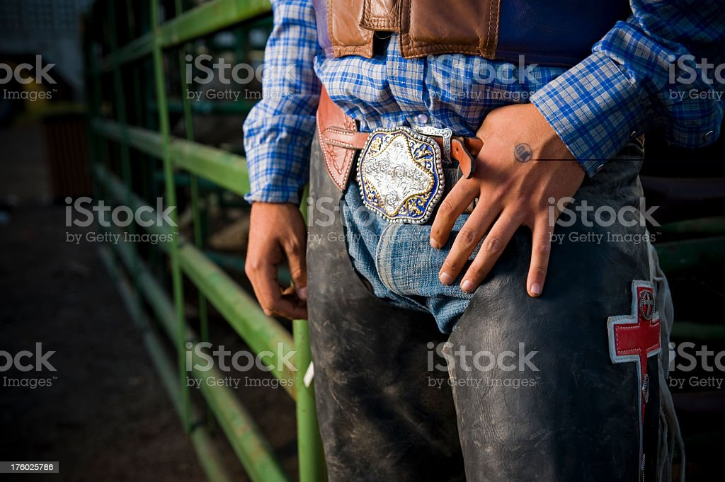 Close up of Rodeo cowboy's hands buckle and chaps Colorado stock photo