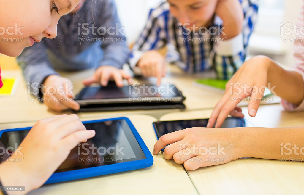 close up of school kids playing with tablet pc stock photo