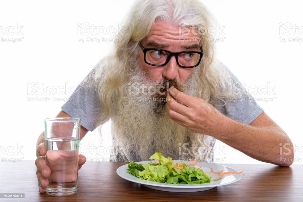 Close up of senior bearded man thinking and wearing eyeglasses while eating plate of salad with glass of water on wooden table stock photo