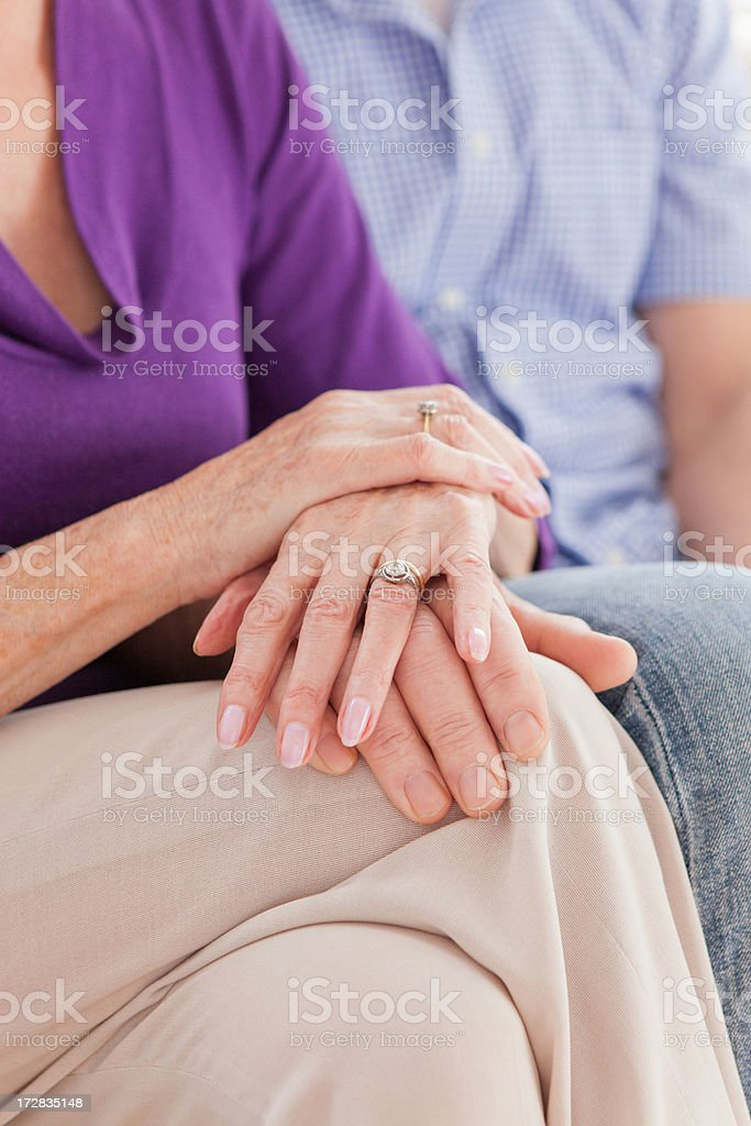 Close up of senior couple touching hands stock photo