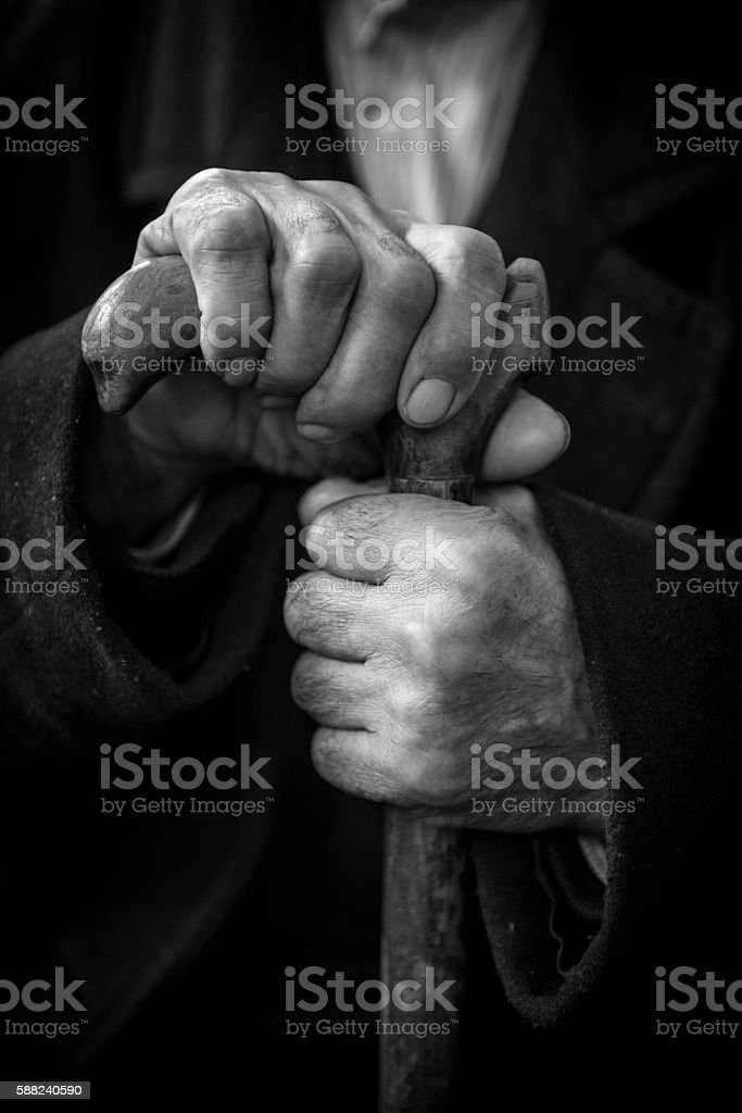 Close up of senior man's hands on cane stock photo