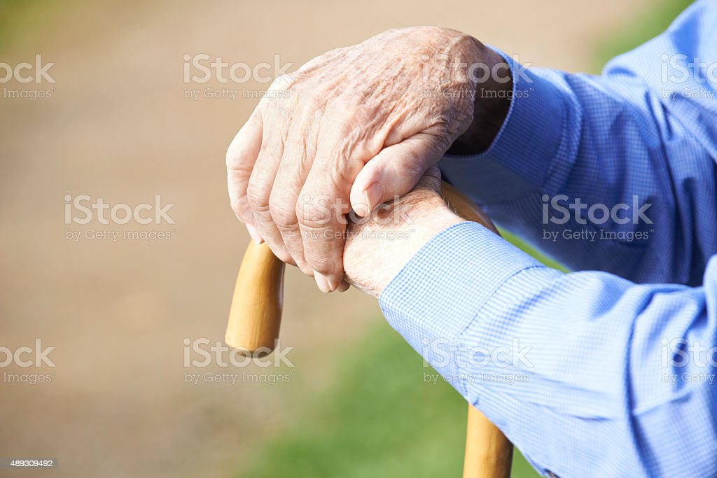 Close Up Of Senior Man's Hands Resting On Walking Stick stock photo