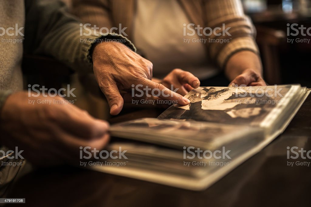 Close up of senior people remembering their old photos. stock photo