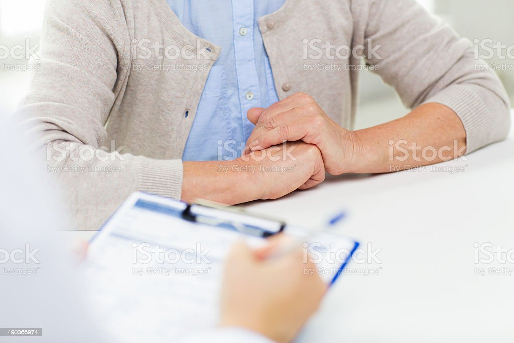 close up of senior woman and doctor with clipboard stock photo