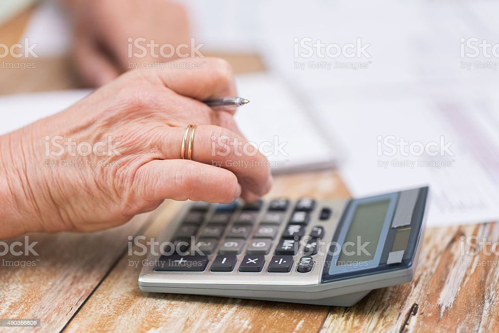 close up of senior woman counting with calculator stock photo