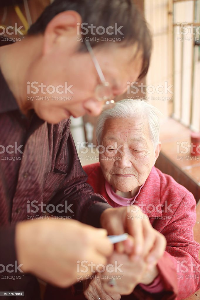 Close Up Of Senior Woman Getting Nails Trimmed stock photo