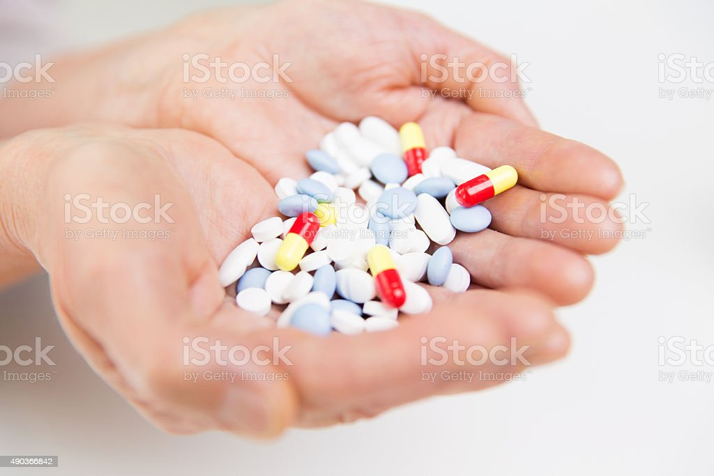 close up of senior woman hands with pills stock photo