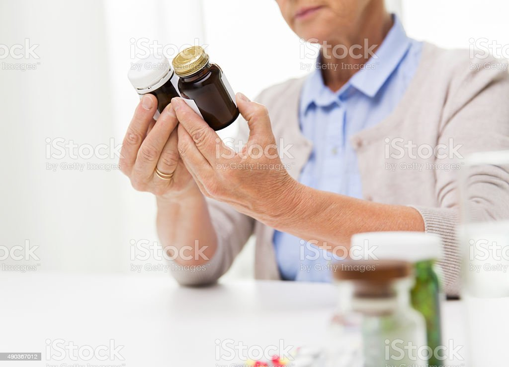 close up of senior woman with medicine jars stock photo