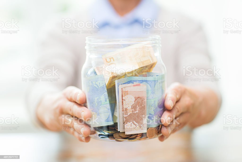 close up of senior woman with money in glass jar stock photo