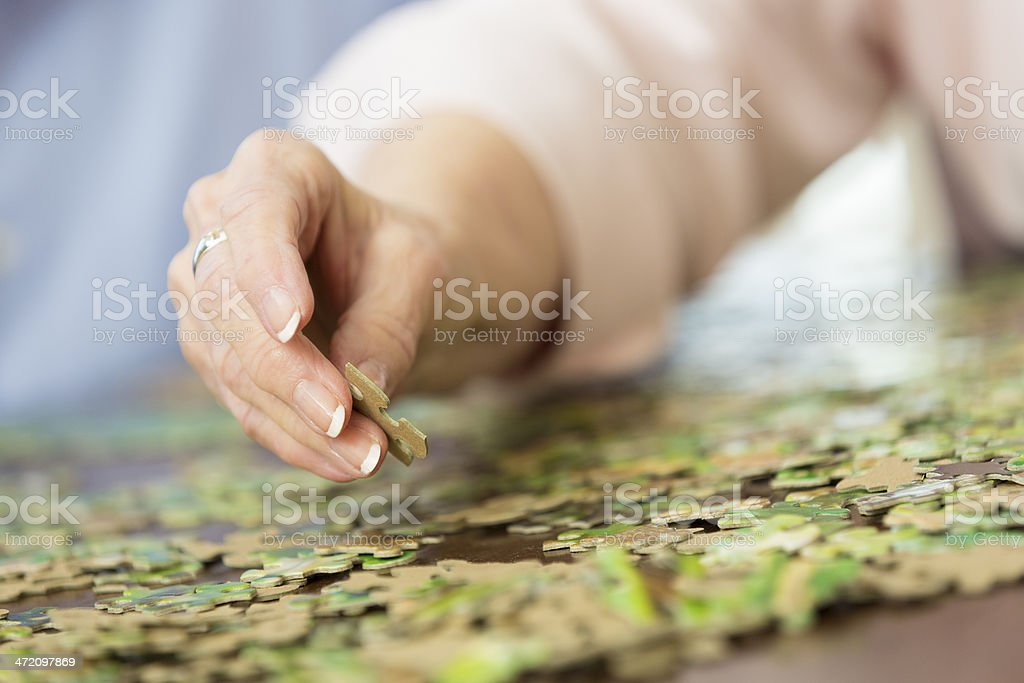 Close up of senior woman's hand putting together puzzle stock photo