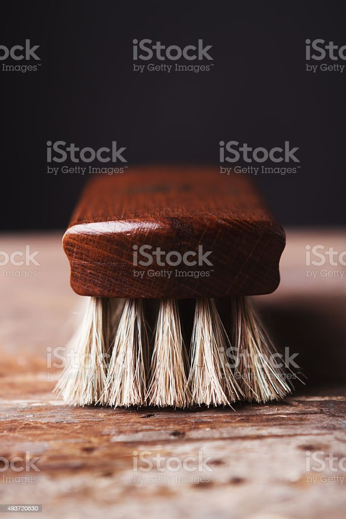 Close up of shoe shine brush on a rustic background stock photo