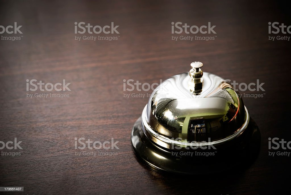 Close up of silver service bell on dark wooden desk stock photo