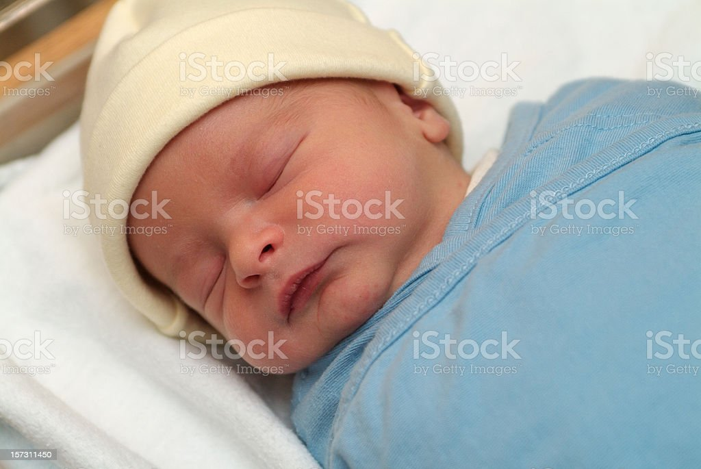 Close up of sleeping newborn baby in blue blanket stock photo
