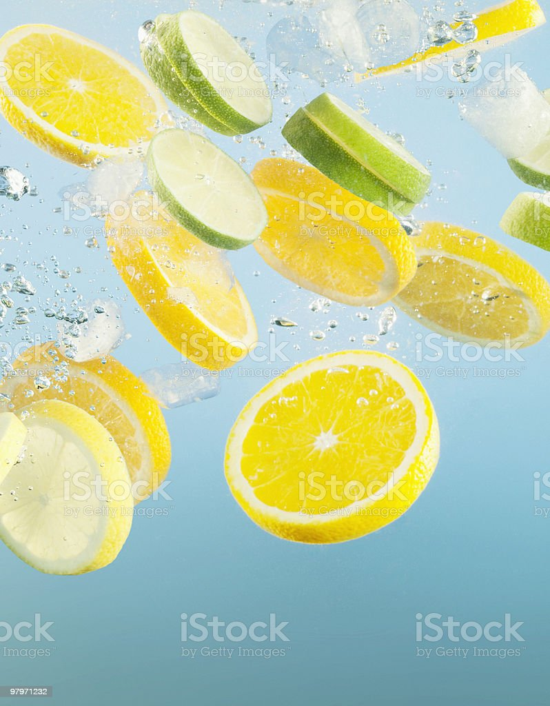 Close up of sliced lemons and limes splashing in water stock photo