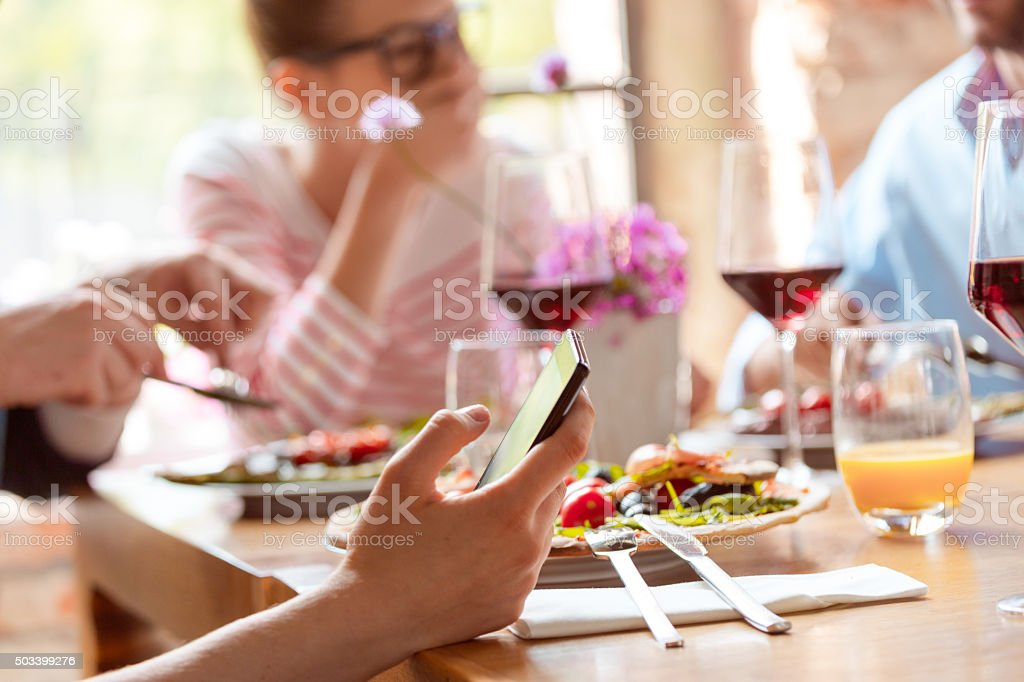 Close up of smart phone in hand during lunch stock photo