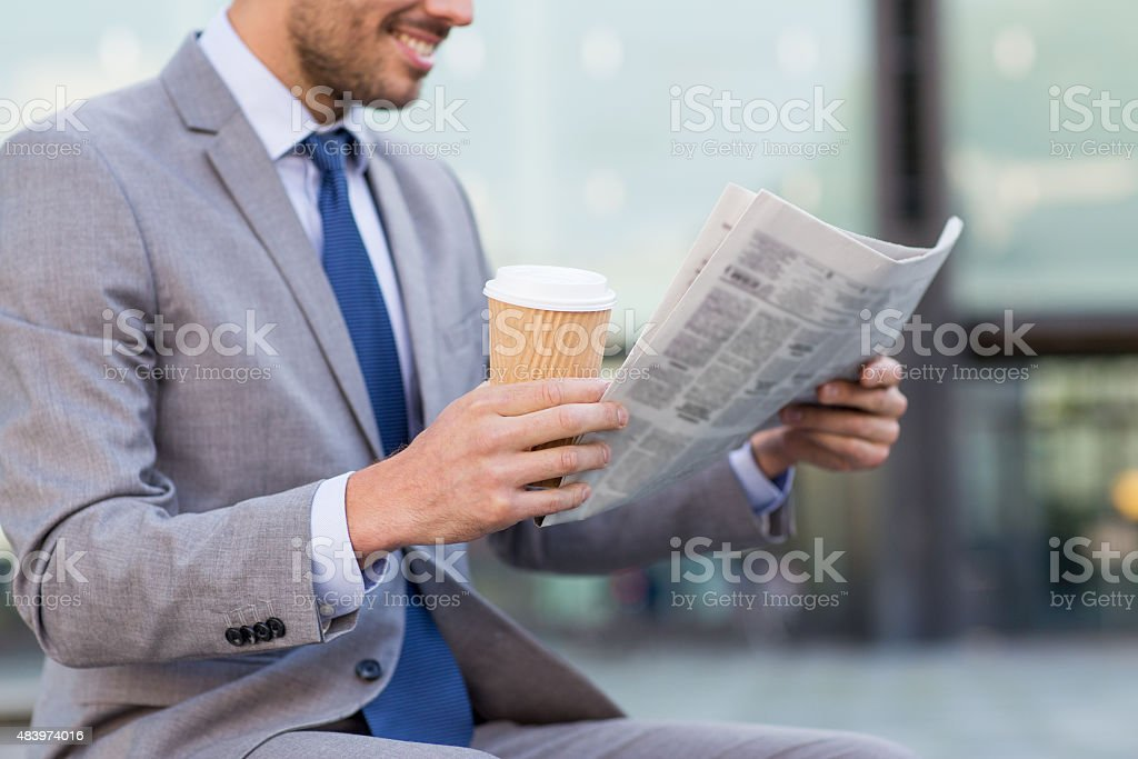 close up of smiling businessman reading newspaper stock photo