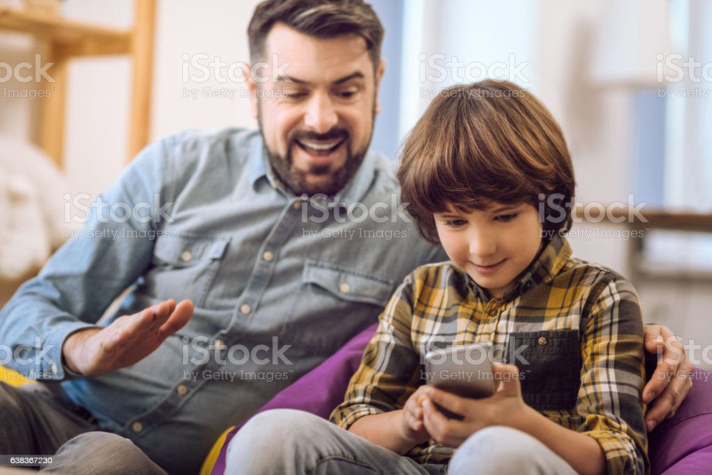 Close up of smiling father playing with son stock photo