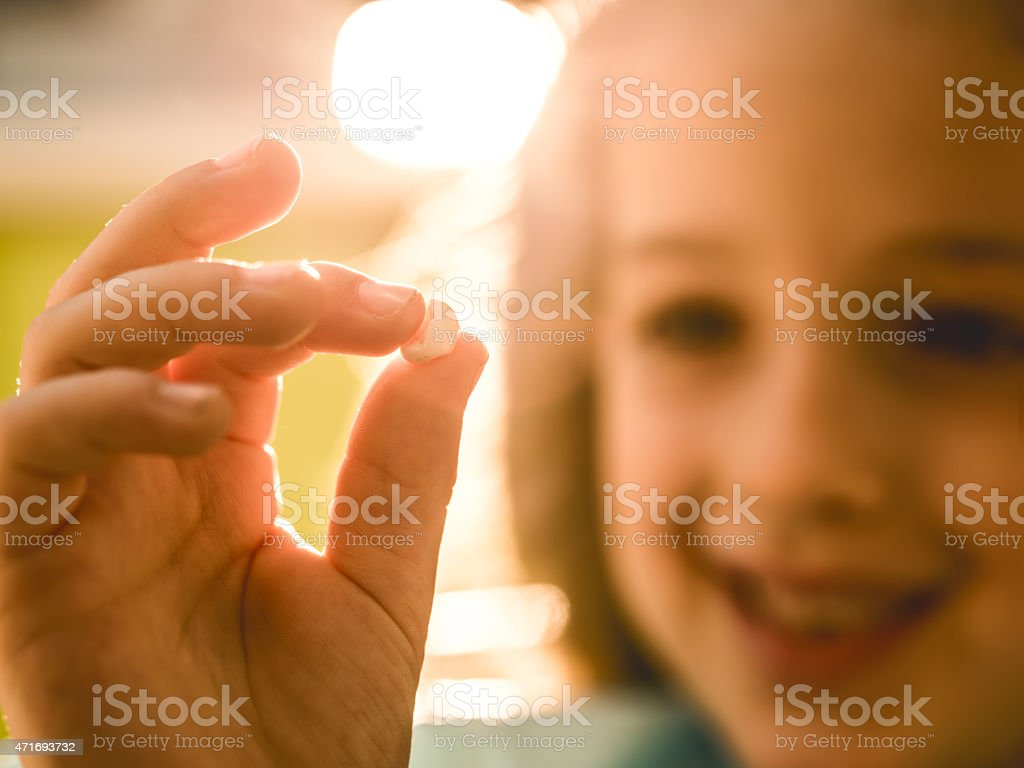 Close up of smiling little girl holding her tooth. stock photo