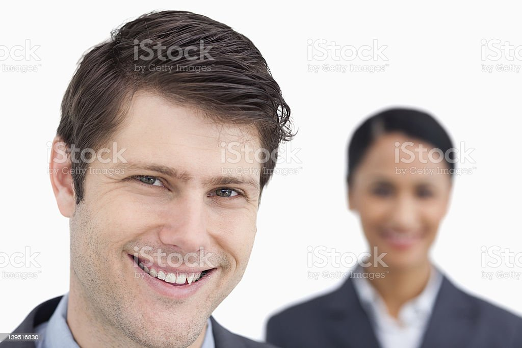 Close up of smiling salesman with colleague behind him stock photo