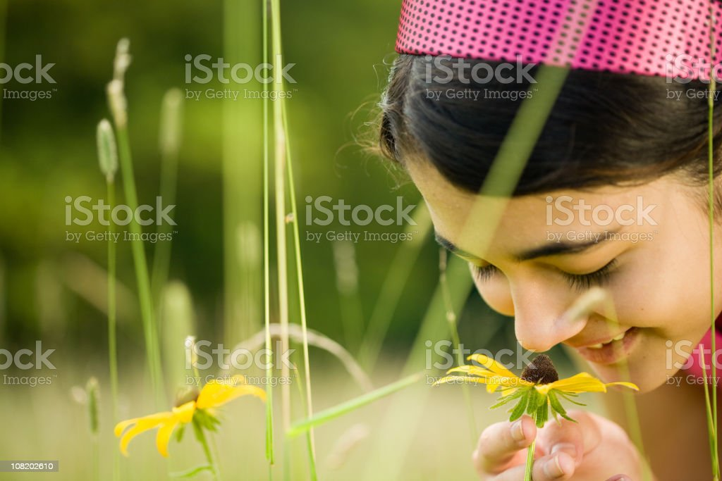 Close up of smiling teen girl smelling a Black-Eyed Susan royalty-free stock photo