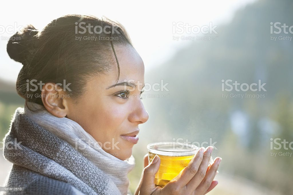 Close up of smiling woman drinking tea outdoors stock photo