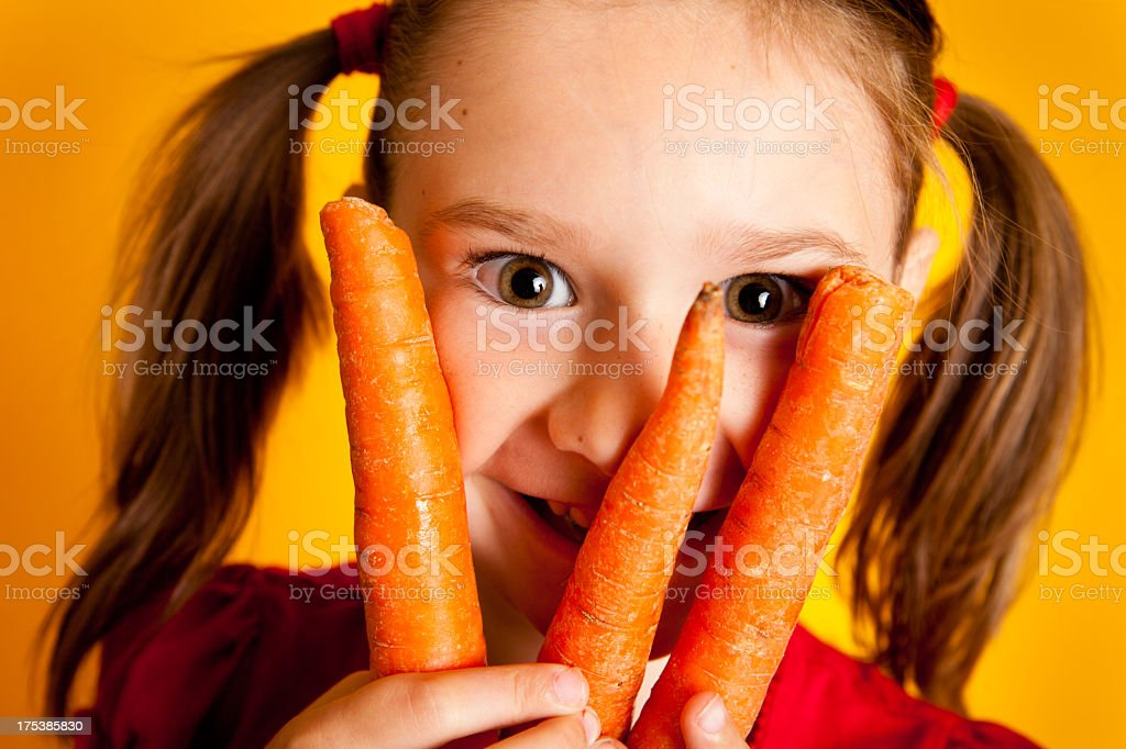 Close Up of Smiling Young Girl Holding Three Carrots royalty-free stock photo