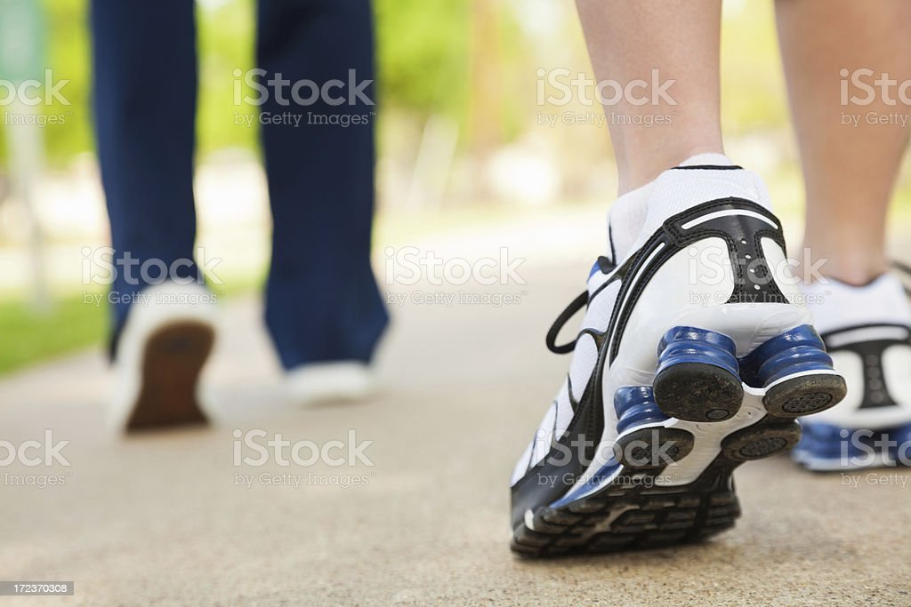 Close up of sneakers; women walking in park stock photo