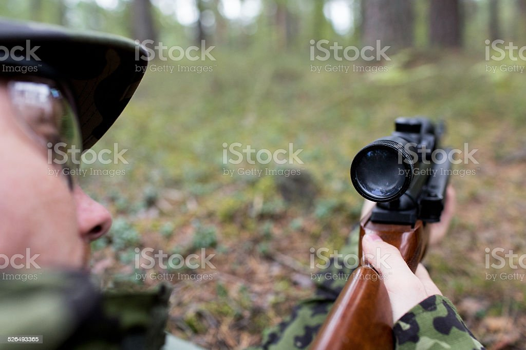close up of soldier or hunter with gun in forest stock photo