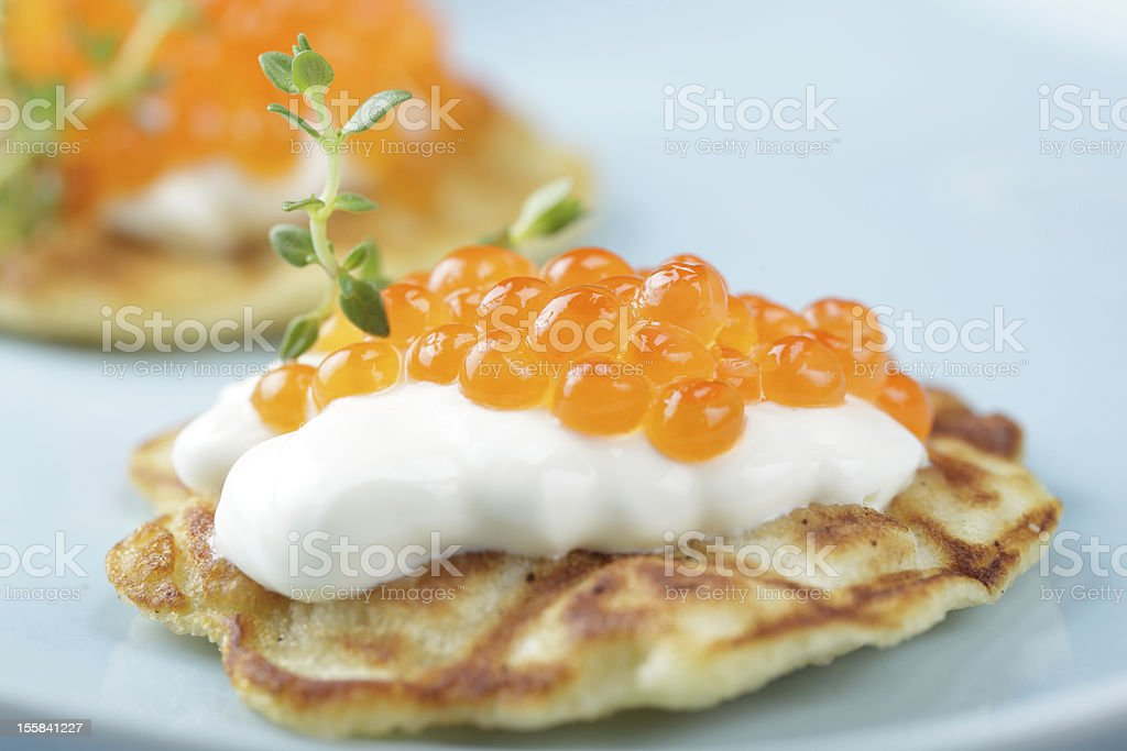 Close up of some blinis with red caviar on a blue plate stock photo