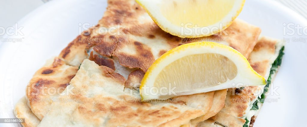 Close Up of Spinach Cheese Turkish Gozleme with Lemon Wedges stock photo