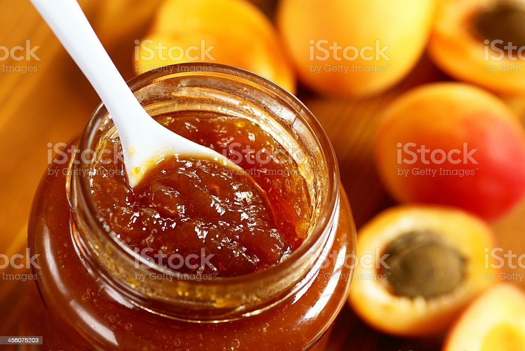 Close up of spoon in open jar of apricot jam with apricots royalty-free stock photo
