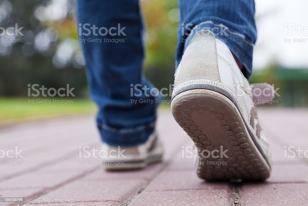 Close up of sports shoes walking on pavement stock photo