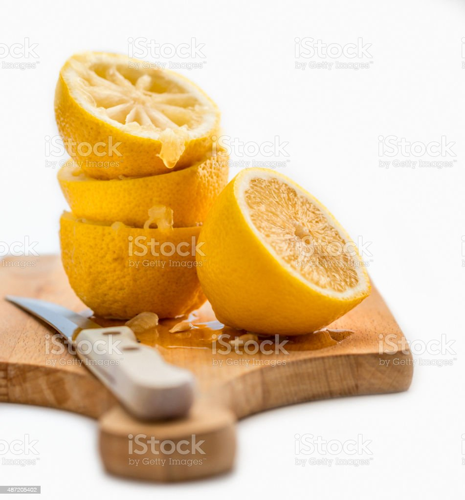 close up of  squeezed lemons  on wooden cutting board stock photo