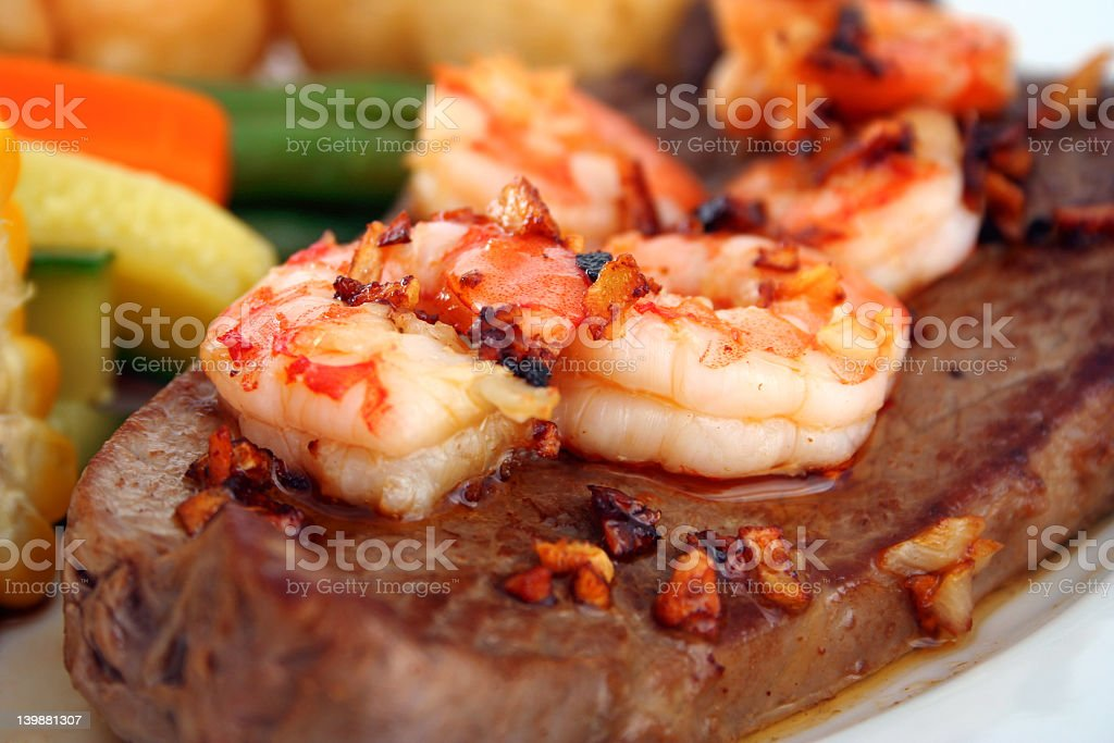 Close up of steak and shrimp surf and turf dinner stock photo