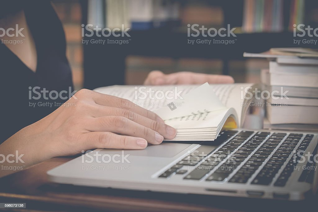 Close up of student hand reading a book at library. stock photo